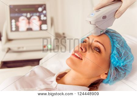 Beautiful female patient is getting a treatment while lying at cosmeticians office