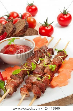 Shish kebab with herbs on a white plate with tomatoes and sauce