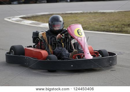 boy is driving Go-kart car with speed in a playground racing track. Go kart is a popular leisure motor sports.