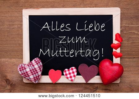 Blackboard With German Text Alles Liebe Zum Muttertag Means Happy Mothers Day. Red Textile Hearts. Wooden Background With Vintage, Rustic Or Retro Style.