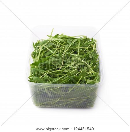 Eruca sativa rucola arugula fresh green rocket salad leaves in a plastic package box, isolated over the white background