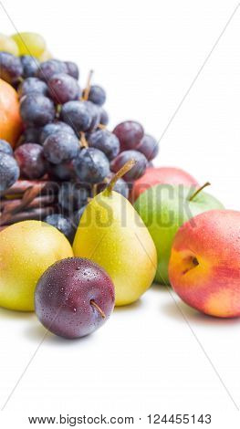 Various fresh ripe fruits placed in a wicker basket and around close up isolated on white background.