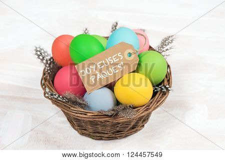 Easter eggs in basket with feather decoration. Happy Easter - JOYEUSES PÀQUES! french text