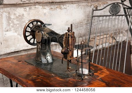 Vintage sewing machine on a wooden table with vintage lamp and white wall in the background