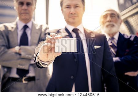 Successful businessmen holding a blank businesscard - Three mature business men in the background white empty card for text ** Note: Shallow depth of field