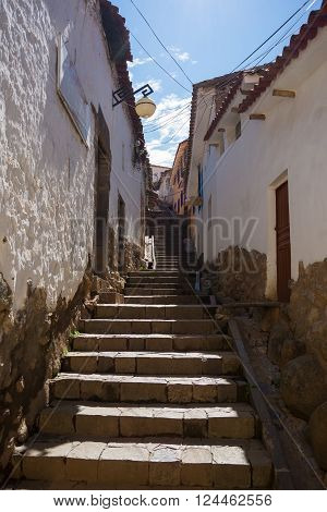 Staircase in a narrow alley of San Blas district, Cusco, Peru, former Inca capital, famous travel destination in the world. Wide angle view from below, morning bright light.