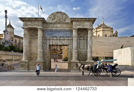 CORDOBA, SPAIN - September 10, 2015: Tourists nearby the Puerta del Puente, a Renaissance gate with a central square passage, sided by two couples of Doric columns, surmounted by a Classic-style entablature on September 10, 2015 in Cordoba, Spain