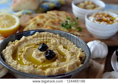 Hummus, close-up of traditional Lebanese chickpea dip served with pita, black olives, garlic, lemon and olive oil.