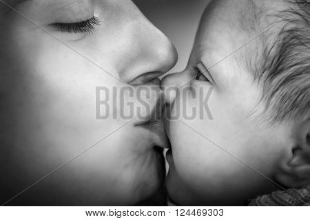 Mother kissing her newborn baby. Close-up portrait, black and white