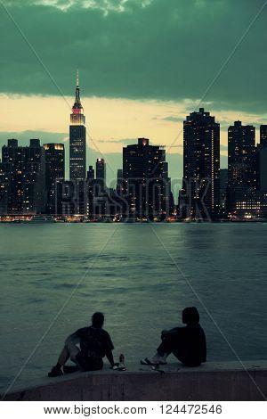 Tow men enjoy Manhattan view at night