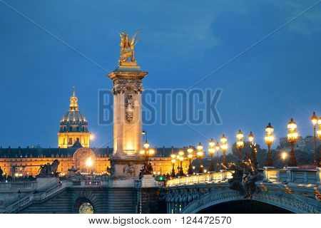 Alexandre III bridge night view with Napoleon's tomb in Paris, France.