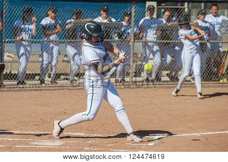 High school softball player hitting the ball.