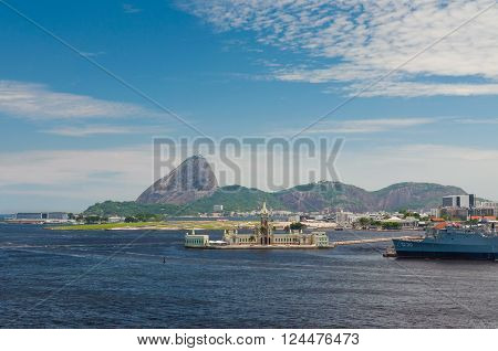 Rio de Janeiro Brazil - December 20 2012: Ilha Fiscal in the foreground is an island located within Guanabara Bay bordering the historic city center of Rio de Janeiro in Brazil. Santos Dumont Airport in the center. Sugarloaf in the background.