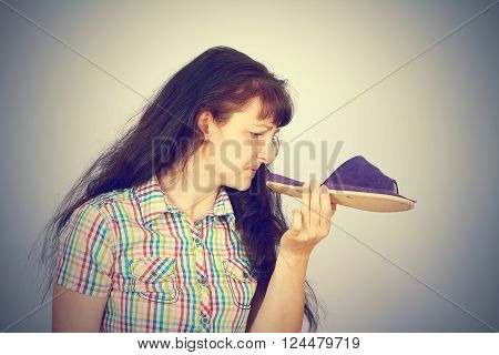 Young Woman Sniffs Smelly Slippers.