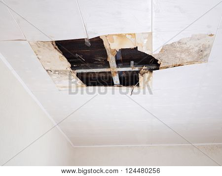 Ceiling panels damaged huge hole in roof from rainwater leakage.Water damaged ceiling . poster