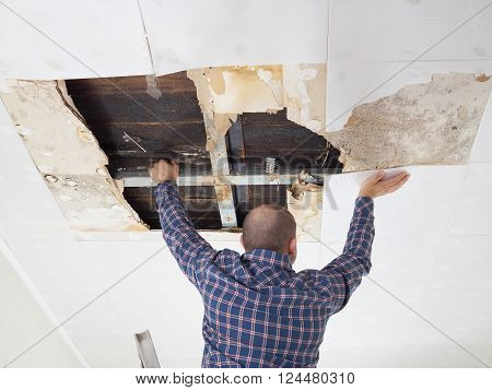 Man repairing collapsed ceiling. Ceiling panels damaged huge hole in roof from rainwater leakage.Water damaged ceiling . poster