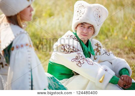 A man on the grass in the traditional attire looks at his beloved woman