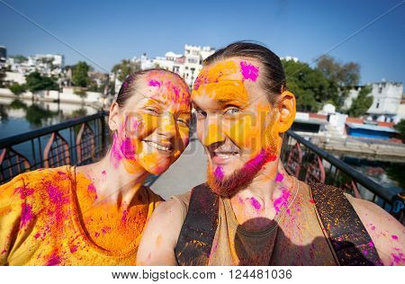 Selfie photo tourist couple with painted face celebrating the colorful festival of Holi on the street of Udaipur Rajasthan India