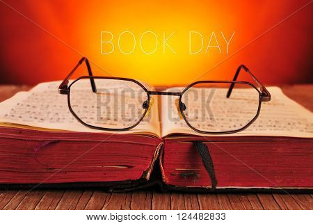 a pair of eyeglasses on an open old book placed on a rustic wooden table, and the text book day against a faded background