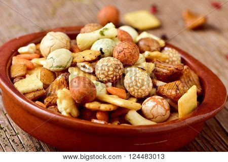 closeup of an earthenware bowl with a snack mix on a rustic wooden table