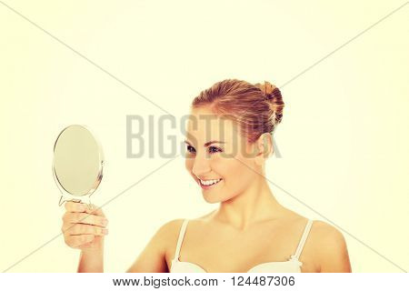 Young beautiful woman looking in a mirror