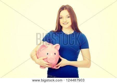 Teenage woman holding piggybank.