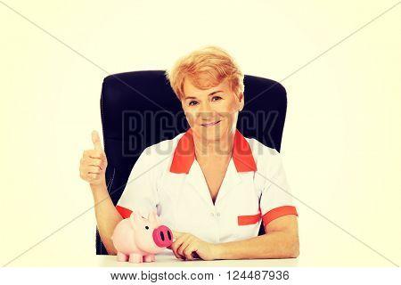 Smile elderly female doctor or nurse sitting behind the desk with piggybank