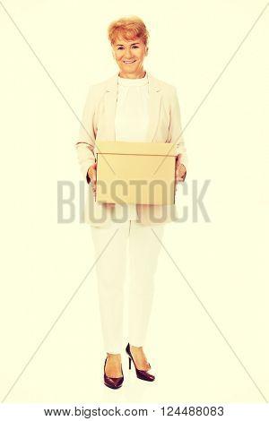 Smile elderly business woman holding cardboard box