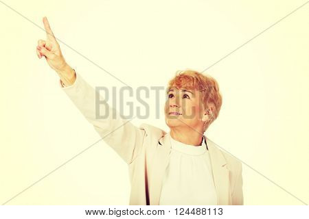 Smile elderly business woman pointing for copyspace or something