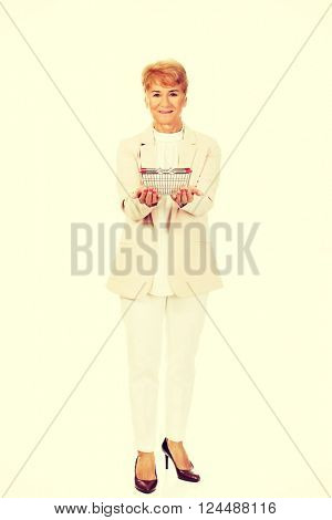 Smile elderly woman holding small shopping basket