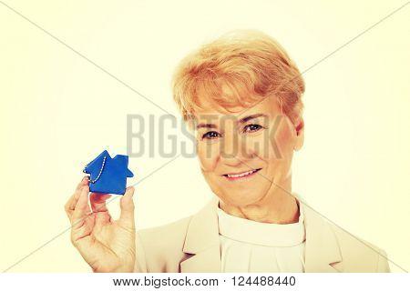 Smile elderly woman holding blue key pendant