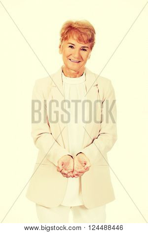 Happy elderly business woman holding copyspace or something on open palms