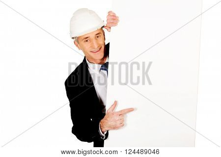 Businessman with hard hat holding empty banner
