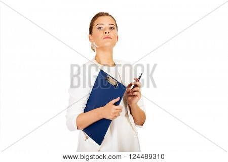 Businesswoman holding a clipboard and thinking about something