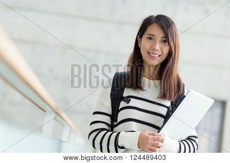 Student holding with lap top computer inside school campus building