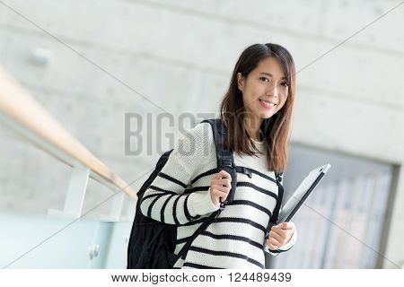 Young woman holding with laptop computer inside modern building