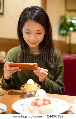 Woman use of cellphone to take photo on her dessert