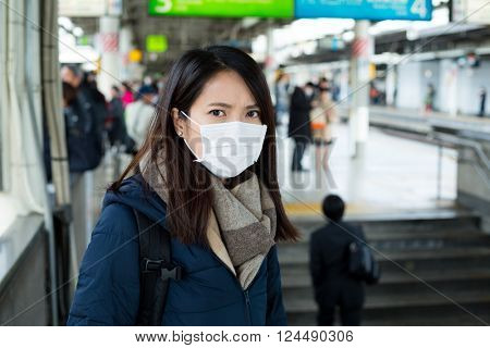 Woman wear face mask in train station