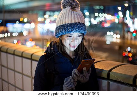 Woman using mobile phone at evening in Tokyo city