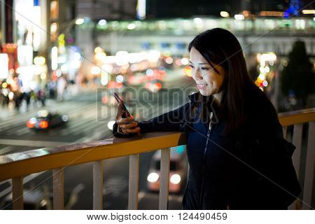 Woman using cellphone at evening