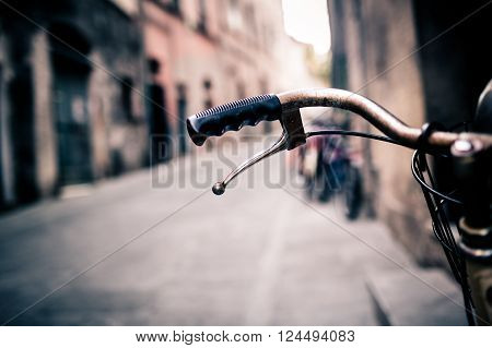 City old bicycle handlebar and basket over blurred background with narrow urban or town street. Vintage retro style bike with bokeh copy space.