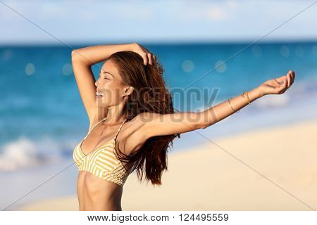 Carefree freedom joy bikini woman happy on beach feeling free with arms up at sunset on ocean background. Portrait of sexy body Asian girl smiling for skincare or weight loss concept.