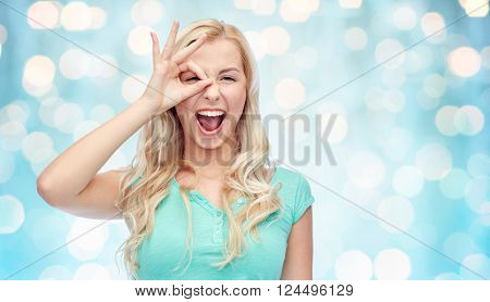 fun, emotions, expressions and people concept - smiling young woman or teenage girl making ok hand gesture over blue holidays lights background