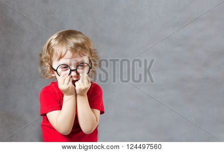 A Child Covers Its Face With A Two Palms.