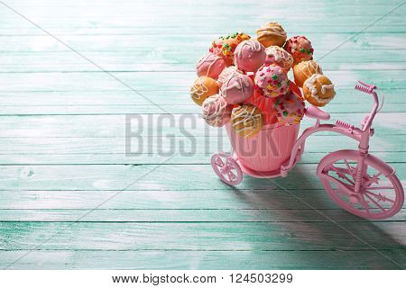 Cake pops in decorative bicycle on turquoise wooden background. Selective focus.Place for text.