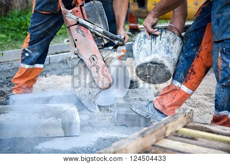 Construction worker cutting concrete paving stabs or metal for sidewalk using a cut-off saw. Profile on the blade of an asphalt or concrete cutter with workers shoes and protective gear.