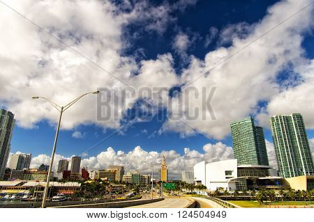 Miami Florida - December 17 2015: Exotic beautiful landscape highway road with green palm trees sky scrapers and cars in sunny weather outdoor on natural blue cloudy sky background