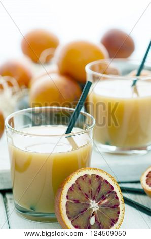 Fresh delicious juice with red oranges on white wooden background selective focus vertical