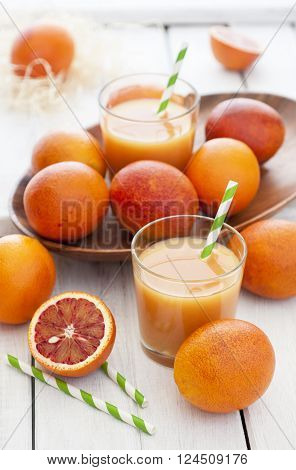 Fresh delicious juice with red oranges on white wooden background selective focus