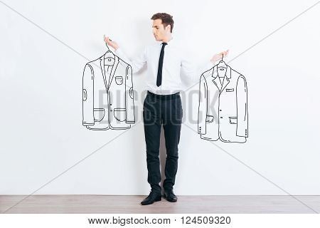 What jacket shall I choose? Handsome young man choosing between two drawn jackets while standing against white background